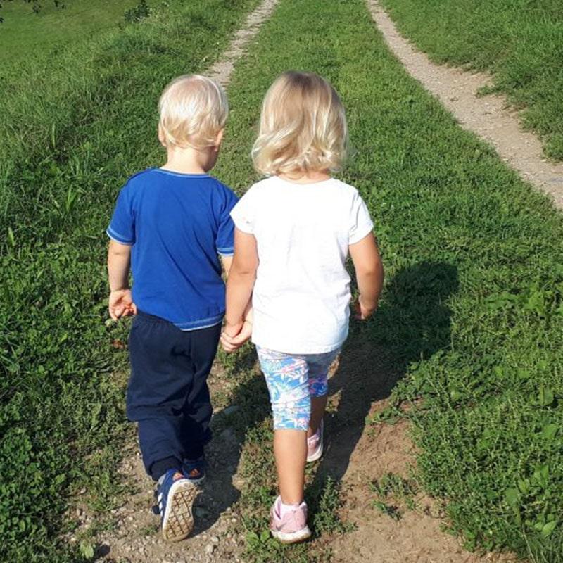 Otroka hodita in se držita za roke