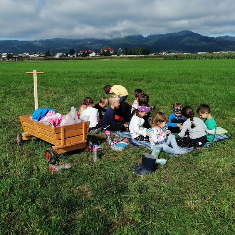Polje z otroci in lesenim vozičkom